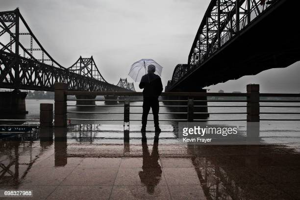 A Chinese man stands in the rain between 'Friendship Bridge' left and 'Broken Bridge' right as he looks across the Yalu river from the border city of...