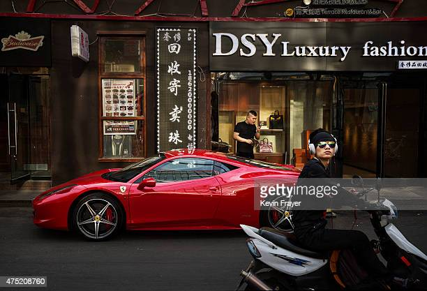 Chinese man stands next to his luxury car as its is parked in an upscale shopping district on May 29 2015 in Beijing China China is expected to...