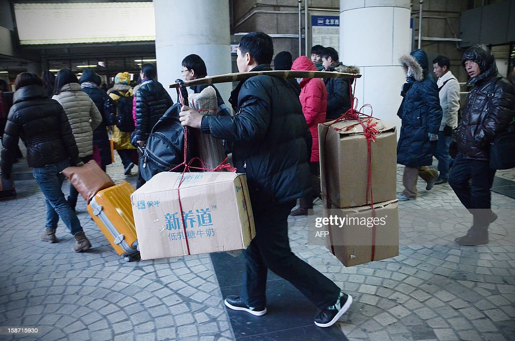 A Chinese man supports his baggage with a shoulder pole as he makes his way at the Beijing west railway station in Beijing on December 26, 2012. China on December 26 started service on the world's longest high-speed rail route, the latest milestone in the country's rapid and sometimes troubled super fast rail network.