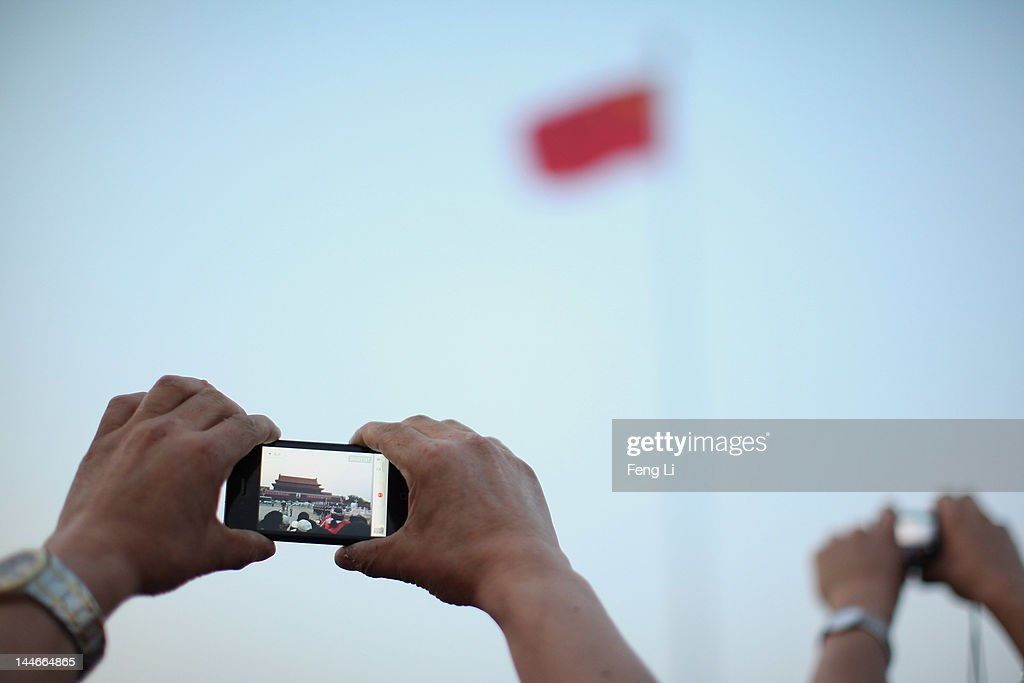 A Chinese man take pictures with his iPhone during the customary ceremony of lowering flag at Tiananmen Square on May 17, 2012 in Beijing, China.