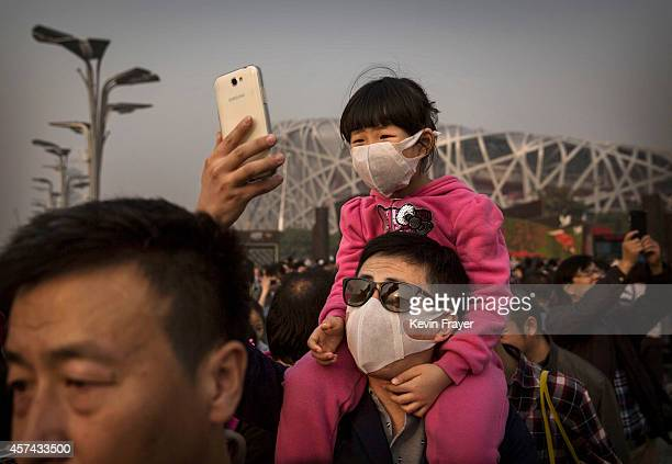 Chinese man takes a picture as he and his daughter wear masks to protect against pollution at the Long Ma Performance by the French company La...
