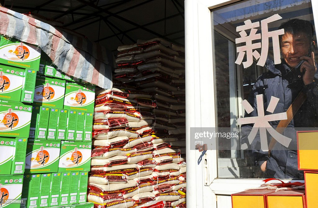 A Chinese man talks on a phone as he waits for customers at his rice stall in a food market in Beijing on November 16 2010 China's central bank...