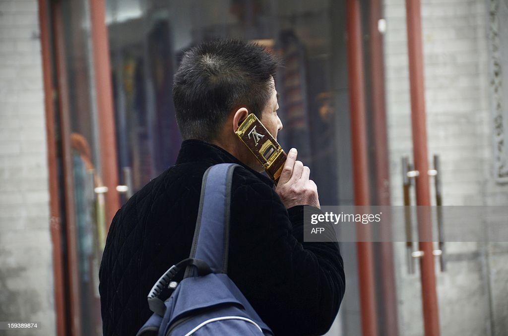 A Chinese man uses his mobile phone as he makes his way along a street in Beijing on January 13,2013. China's economy is poised finally to end a long downward trend in 2013, economists polled by AFP say, as the new communist leadership vows to retool the nation's investment-led development model and promote a 'happy life' for all.