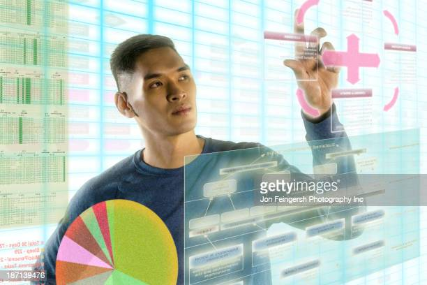 Chinese man using illuminated touch screen
