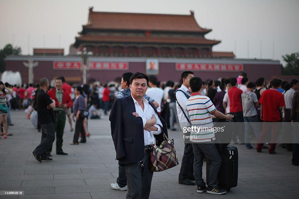 A Chinese man waits before the customary ceremony of lowering flag at Tiananmen Square on May 17, 2012 in Beijing, China.
