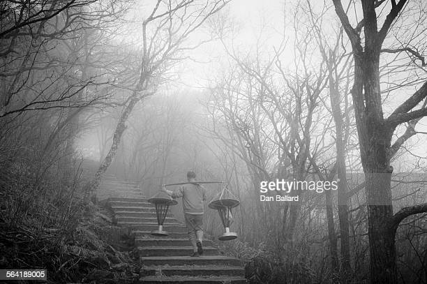 Chinese man walking up stairs into fog. Yellow Mountain (Mt. Huangshan), China.