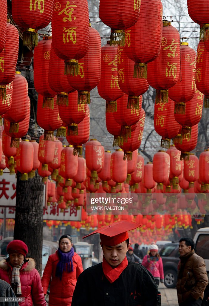 A Chinese man walks beneath lanterns as the city prepares for the traditional Lantern Festival which falls on the 15th day of the Lunar New Year and officially ends the celebrations, in Beijing on February 21, 2013. The festival which dates back more than 2000 years to the Han Dynasty sees China's cities becoming a sea of lanterns and fireworks. AFP PHOTO/Mark RALSTON