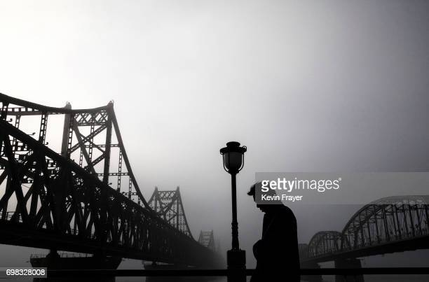 A Chinese man walks in the rain between 'Friendship Bridge' left and 'Broken Bridge' right as he looks across the Yalu river from the border city of...