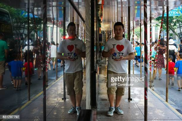 A Chinese man walks near shopping stores in Shanghai on August 14 2017 China's industrial output a key engine of growth slowed sharply in July as...