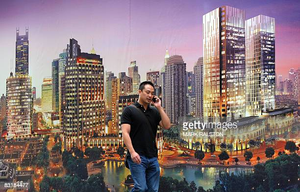 A Chinese man walks past a billboard promoting a new property development under construction in Shanghai on October 9 2008 China's presence on the...