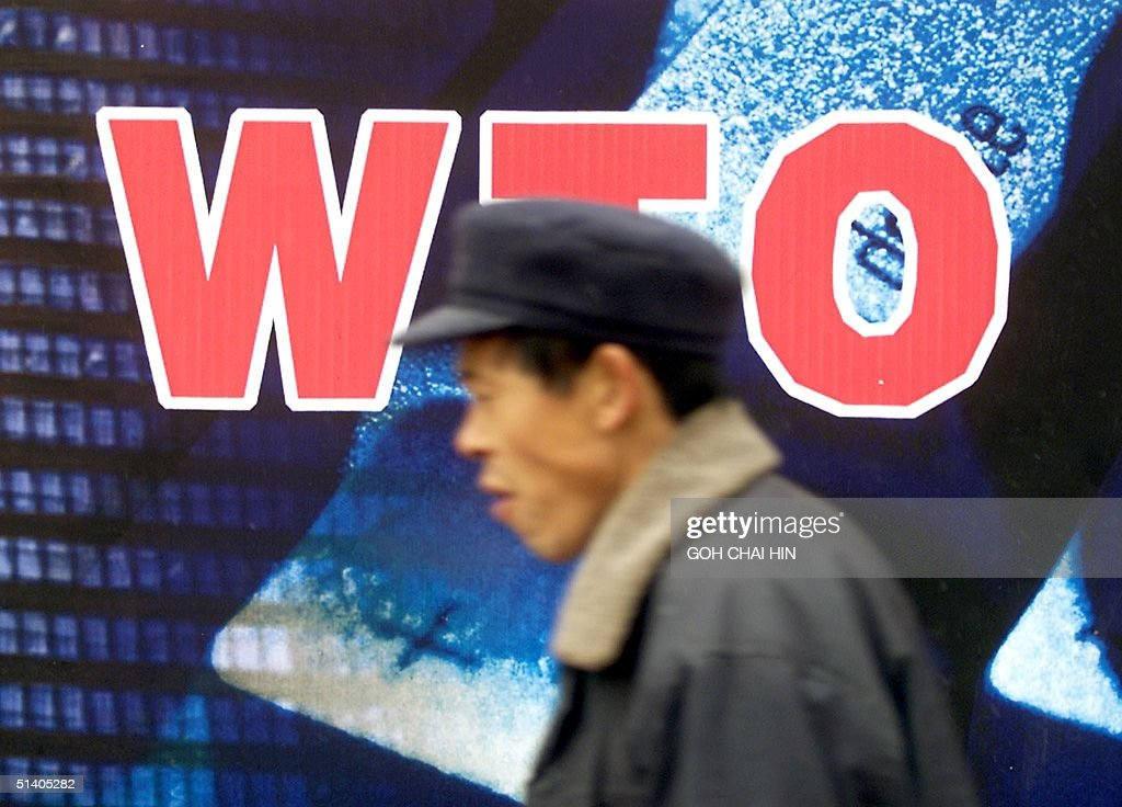 Chinese man walks past a billboard welcoming the country's membership to the World Trade Organisation in Beijing 10 December 2001 After 15 years of...