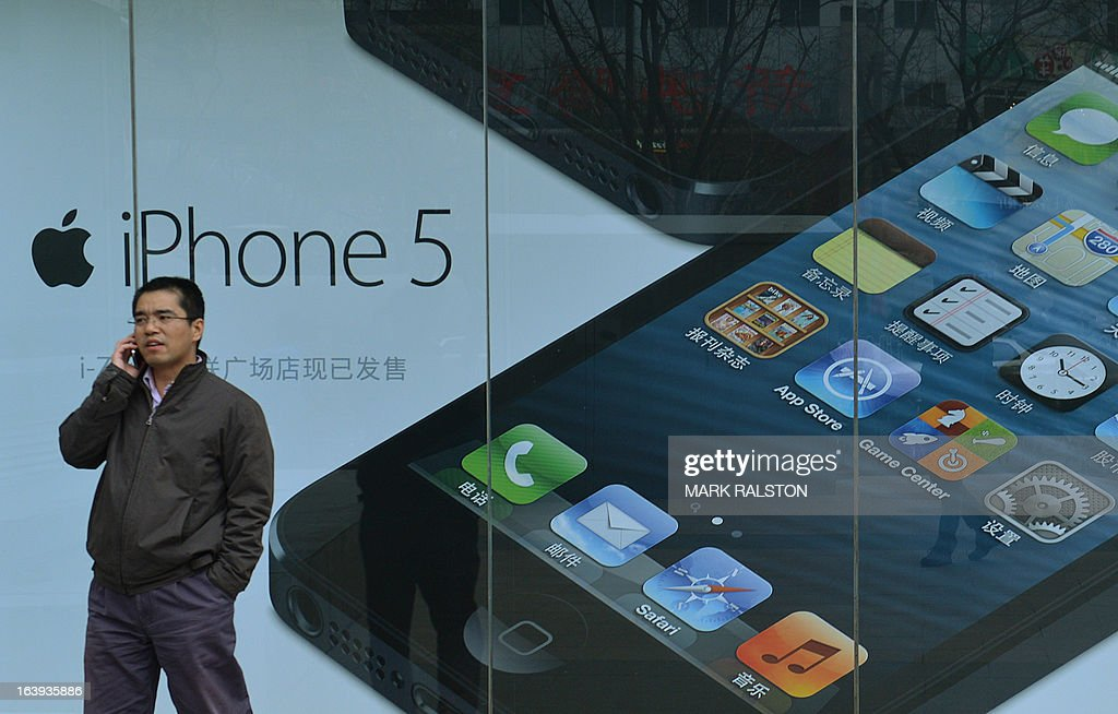 A Chinese man walks past an advertisement for an IPhone outside an Apple reseller in Beijing on March 18, 2013. Apple was recently targeted over its consumer-service practices in China during a state television broadcast focusing on consumer rights, allegedly claiming the US company treated its Chinese customers differently than in other countries when it came to product service and warranties. A storm or criticism, both pro and against, swamped social media websites in the aftermath of the broadcast. China is the second-biggest market for Apple after the United States. AFP PHOTO / MARK RALSTON