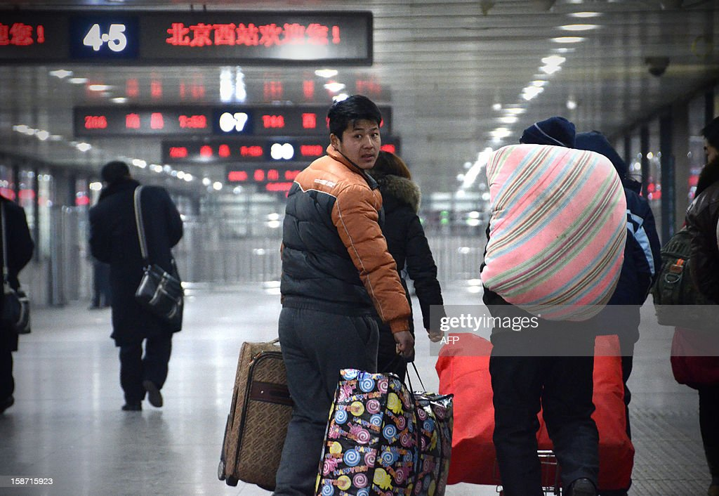 A Chinese man walks with his luggage at the Beijing west railway station in Beijing on December 26, 2012. China on December 26 started service on the world's longest high-speed rail route, the latest milestone in the country's rapid and sometimes troubled super fast rail network.