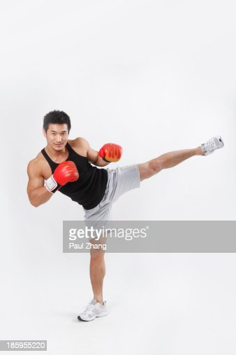 Chinese man wearing boxing gloves in gym : Stock Photo