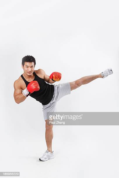 Chinese man wearing boxing gloves in gym
