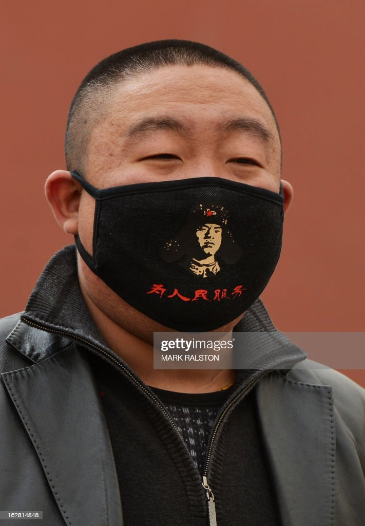 A Chinese man wears a facemask bearing the image of legendary and self-sacrificing soldier Lei Feng as Beijing is hit by a sandstorm as well as air quality worse than the highest classification of 'hazardous' on February 28, 2013. China celebrates the 50th anniversay of the 'Learn from Lei Feng' self-sacrifice and devotion to the party campaign this year. State media reported that Beijing air pollution levels reached extremely hazardous levels for the second time this week as citizens struggled to protect themselves from the two-pronged hazards of dust and pollution. AFP PHOTO/Mark RALSTON