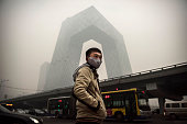 Chinese man wears a mask as he waits to cross the road near the CCTV building during heavy smog on November 29 2014 in Beijing China United States...