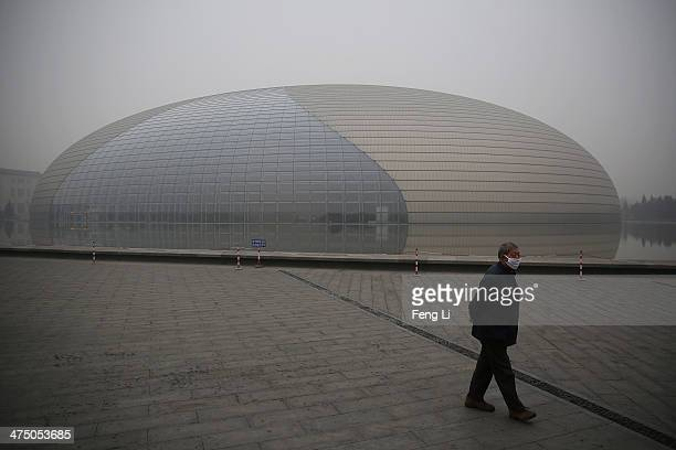 Chinese man wears a mask outside National Grand Theater during dangerous levels of air pollution on February 26 2014 in Beijing China The air...
