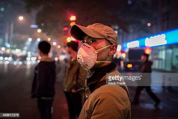 Chinese man wears a mask to protect against air pollution as he waits to cross the road on a smoggy evening on November 26 2014 in Beijing...