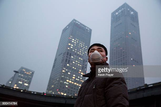 Chinese man wears a mask to protect against pollution in heavy smog on December 8 2015 in Beijing China The Beijing government issued a 'red alert'...