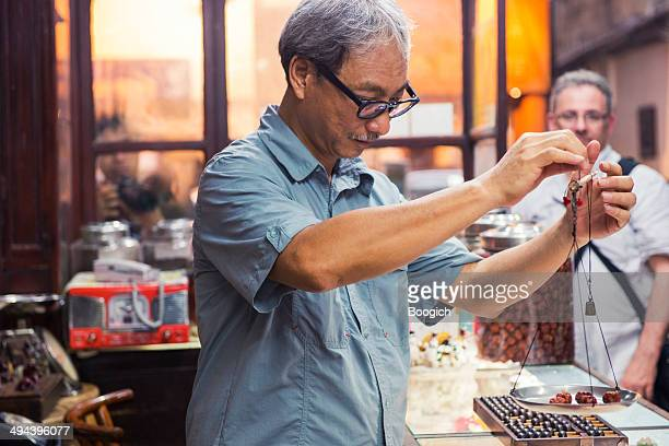 Chinese Man Weighs Herbs in Kowloon Medicine Shop Hong Kong