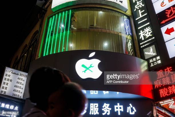 A Chinese man works inside a unauthorised Apple mobile workshop in Shanghai on August 15 2017 Trade tensions between the United States and China...