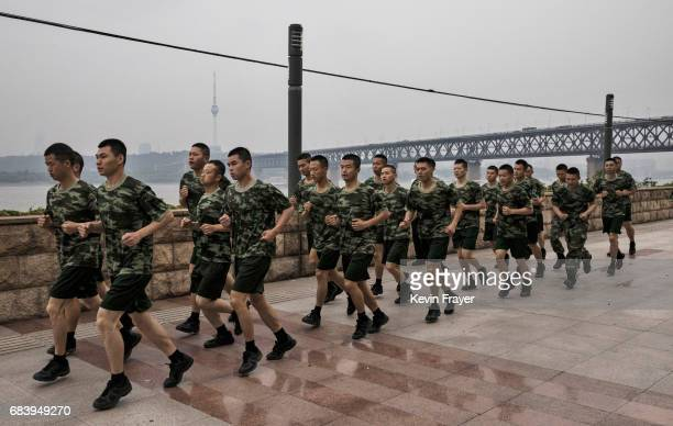 Chinese Marine police run during morning exercise near the Great Bridge on the Yangtze River or Chang Jiang on May 16 2017 in Wuhan Hubei province...