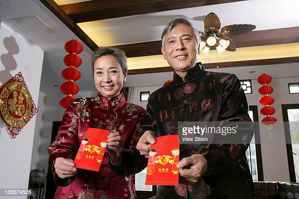 Chinese mature couple making a wish with a red packet
