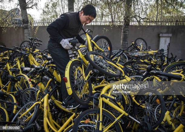 Chinese mechanic from the bike share company Ofo Inc chooses a bike to repair as he stands on a pile of bicycles after they were collected from the...