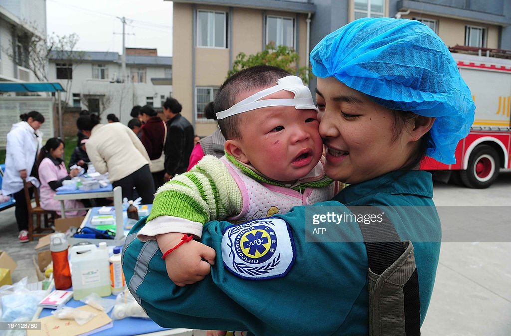 A Chinese medical worker holds an injured child in Longmen township, a town close to the epicentre of the earthquake that hit the city in Ya'an, southwest China's Sichuan province on April 21, 2013. Thousands of rescue workers combed through flattened villages in southwest China on Sunday in a race to find survivors from a powerful quake as the toll of dead and missing rose past 200. CHINA