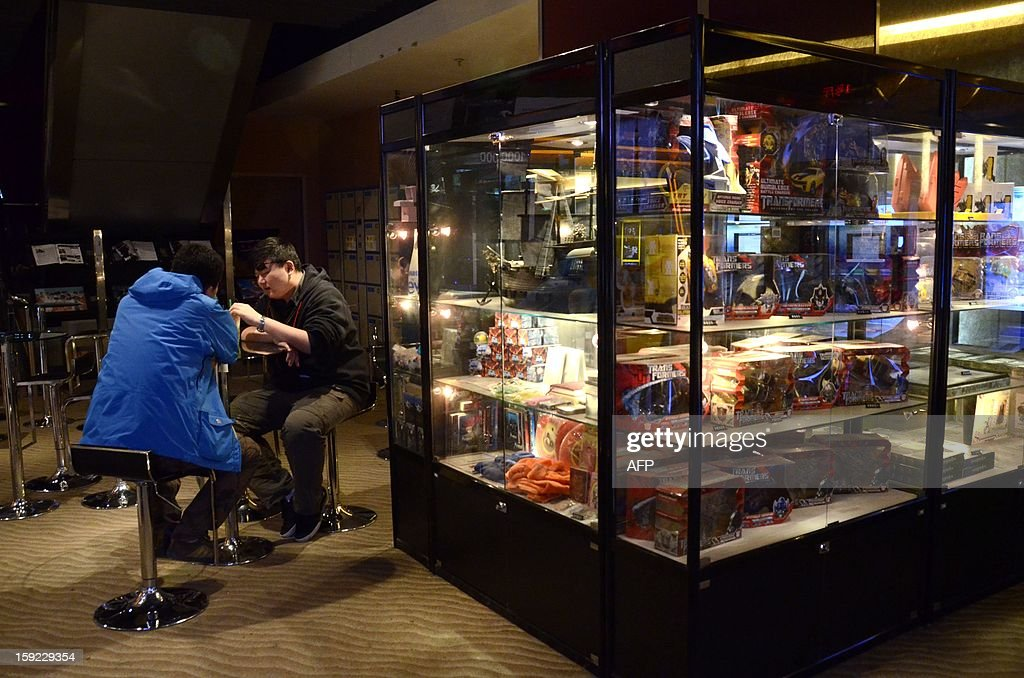 Chinese men chat as they sit near a cabinet of toys based on the characters of the US movie 'Transformers' in a cabinet (R) at a cinema in Beijing on January 10, 2013. Moviegoers in China spent 17 billion yuan (2.7 billion USD) on tickets last year, turning the country into the second-largest film market in the world, the state news agency Xinhua said on January 9. AFP PHOTO / WANG ZHAO