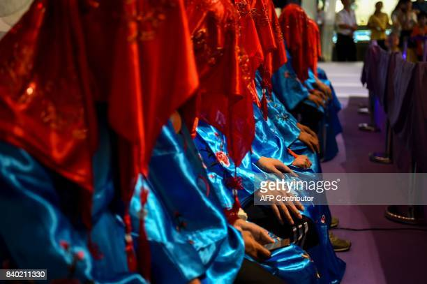 Chinese men cover their face during a competition as their girlfriends try to recognise them during the Qixi Festival or Chinese Valentine's Day in...