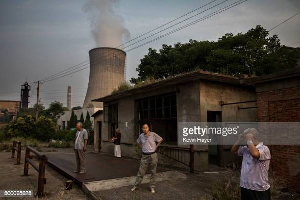 Chinese men exercise under a cooling tower at a coal fired power plant near the site of a large floating solar farm project under construction by the...