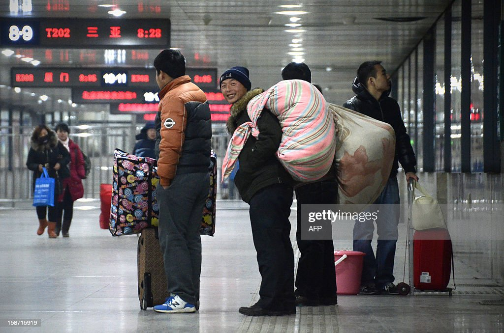 Chinese men hold their luggage at the Beijing west railway station in Beijing on December 26, 2012. China on December 26 started service on the world's longest high-speed rail route, the latest milestone in the country's rapid and sometimes troubled super fast rail network. AFP PHOTO / WANG ZHAO