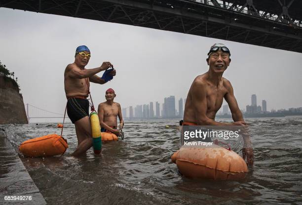 Chinese men prepare for their morning swim under the Great Bridge in the Yangtze River or Chang Jiang on May 16 2017 in Wuhan Hubei province China