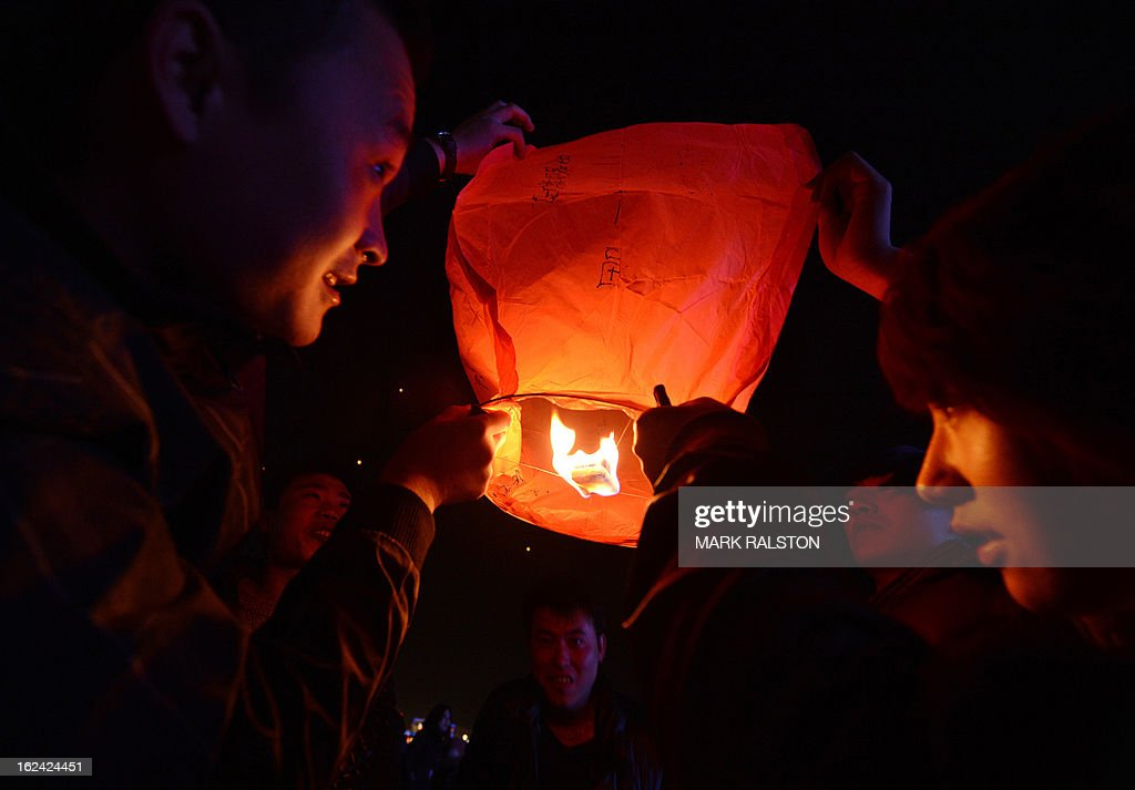 Chinese men release a paper lantern into the sky on the eve of the traditional Lantern Festival which falls on the 15th day of the Lunar New Year and officially ends the celebrations, in Yuxian on February 23, 2013. The festival which dates back more than 2000 years to the Han Dynasty sees China's cities become a sea of lanterns and fireworks. AFP PHOTO/Mark RALSTON