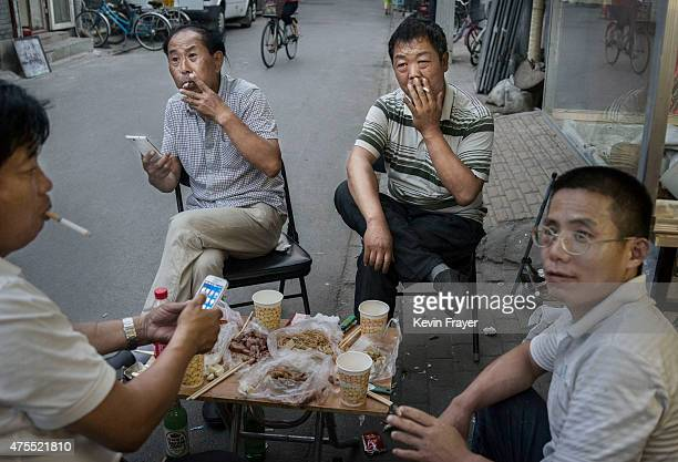 Chinese men smoke together as they eat in the street on June 1 2015 in Beijing China Beijing introduced strong new measures June 1 banning smoking in...