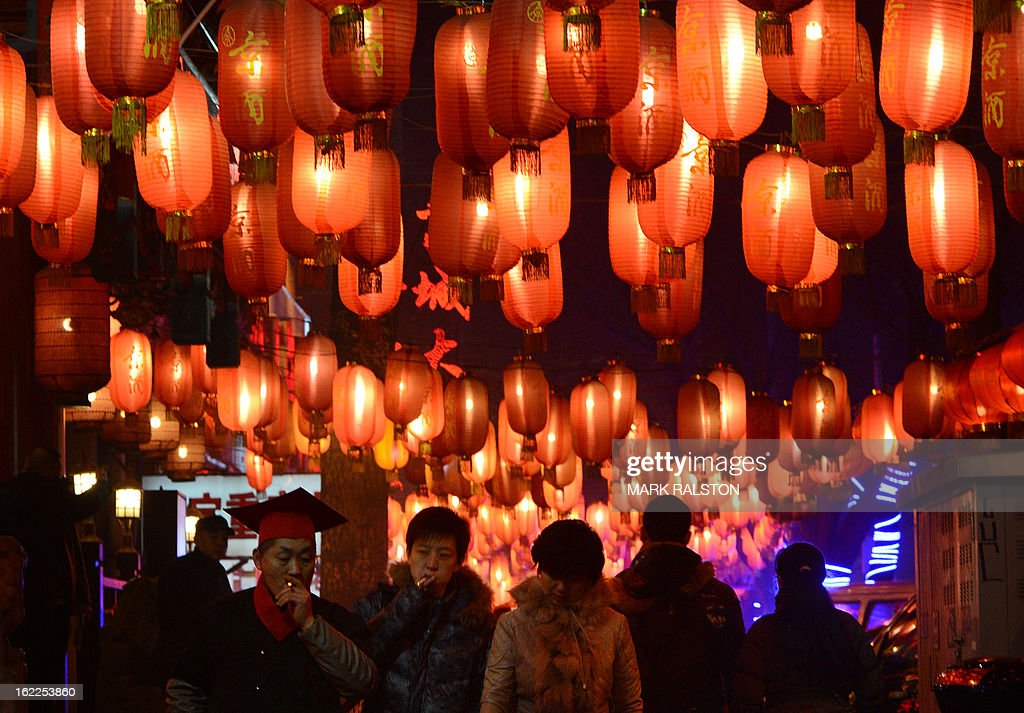Chinese men smoke while walking beneath lanterns as the city prepares for the traditional Lantern Festival which falls on the 15th day of the Lunar New Year and officially ends the celebrations, in Beijing on February 21, 2013. The festival which dates back more than 2000 years to the Han Dynasty sees China's cities becoming a sea of lanterns and fireworks. AFP PHOTO/Mark RALSTON