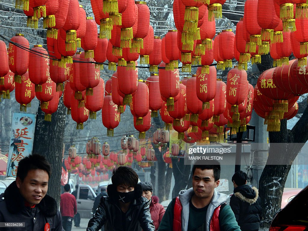 Chinese men walk beneath lanterns as the city prepares for the traditional Lantern Festival which falls on the 15th day of the Lunar New Year and officially ends the celebrations, in Beijing on February 21, 2013. The festival which dates back more than 2000 years to the Han Dynasty sees China's cities becoming a sea of lanterns and fireworks. AFP PHOTO/Mark RALSTON
