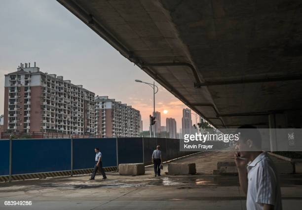 Chinese men walk in the street near a construction site for a new development on May 15 2017 in Wuhan Hubei province China
