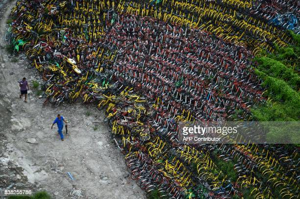 Chinese men walk past the abandoned share bicycles stored at a temporary parking lot in Shanghai on August 24 2017 The bikesharing industry has...