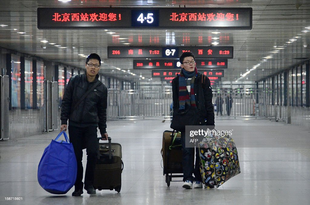 Chinese men walk with their luggage at the Beijing west railway station in Beijing on December 26, 2012. China on December 26 started service on the world's longest high-speed rail route, the latest milestone in the country's rapid and sometimes troubled super fast rail network. AFP PHOTO / WANG ZHAO