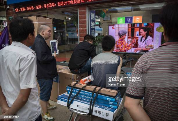 Chinese men watch a program on a large television set in the window of an electronics shop on May 15 2017 in Wuhan Hubei province China