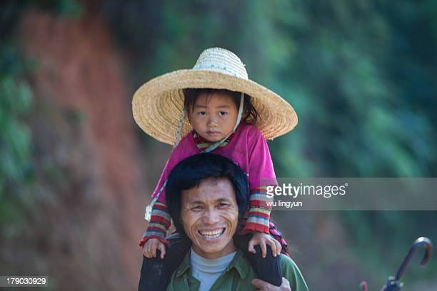 CONTENT] Chinese Miao family with daughter on her father's shoulder were going to the rice fields to work in the morning at Biasha Miao...