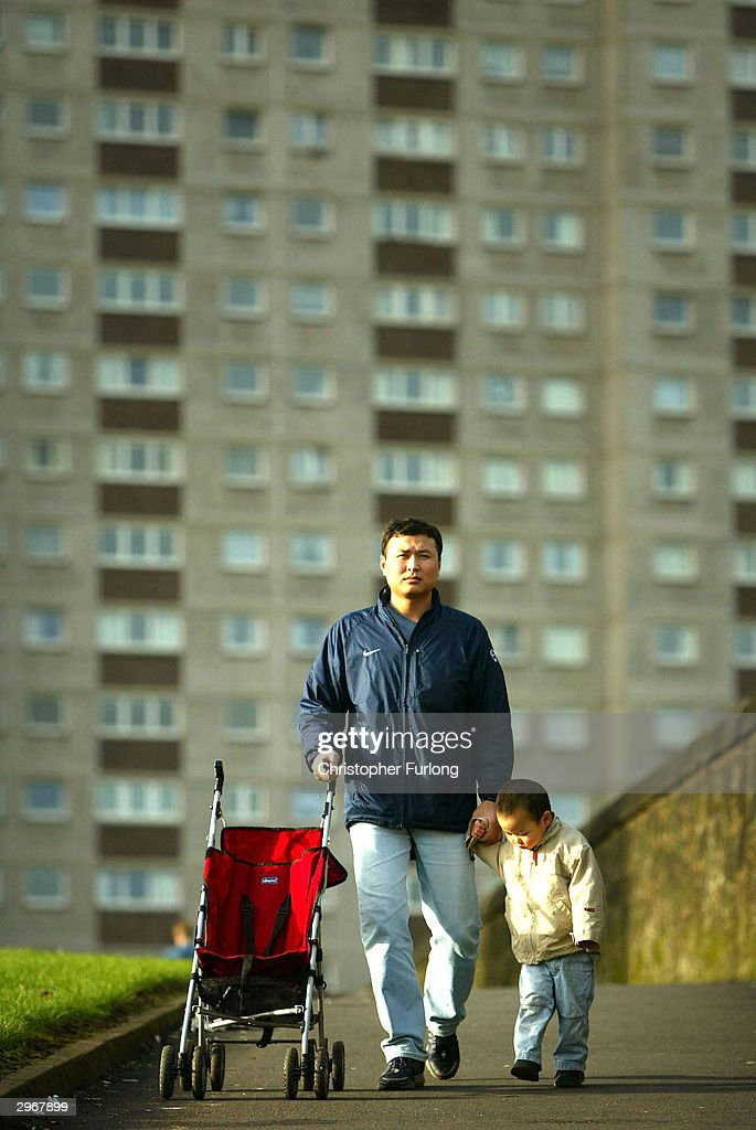 A Chinese migrant walks with his child outside the Sighthill housing estate, February 11, 2004 in Glasgow, Scotland. Scottish authorities are mulling plans to counter the effects of a declining population by encouraging migrants to the country with work permits.