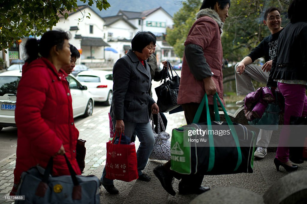 Chinese migrant workers carry their baggages as they employed with 80 RMB yuan(US$12.68) per day to pluck Longjing tea leaves at Meijiawu Village on March 29, 2012 in Hangzhou, China. Longjing is a green-tea, often called Dragon Well tea. The tea is typically picked by hand, and is of a high quality, earning the title of China Famous Tea. The Longjing tea begins to pluck before Chinese traditional Qingming Festival, the 15th day from the Spring Equinox or usually occurring around April 5. Many Chinese migrant workers from Jiangsu, Anhui, Jiangxi and other neighboring provices have been employed with 80 RMB yuan(US$12.68) to 120 RMB yuan(US$ 19.03) per day to pluck fresh Longjing tea leaves for villagers in many Longjing tea production villages in the outskirts of Hangzhou. The price of Longjing tea rose in recent years which aims to become to luxury goods. A high-end Longjing tea in Hangzhou sold for 50,000 RMB yuan(US$ 7930) half a kilo in 2012, the price rose 70 times in the last 12 years.