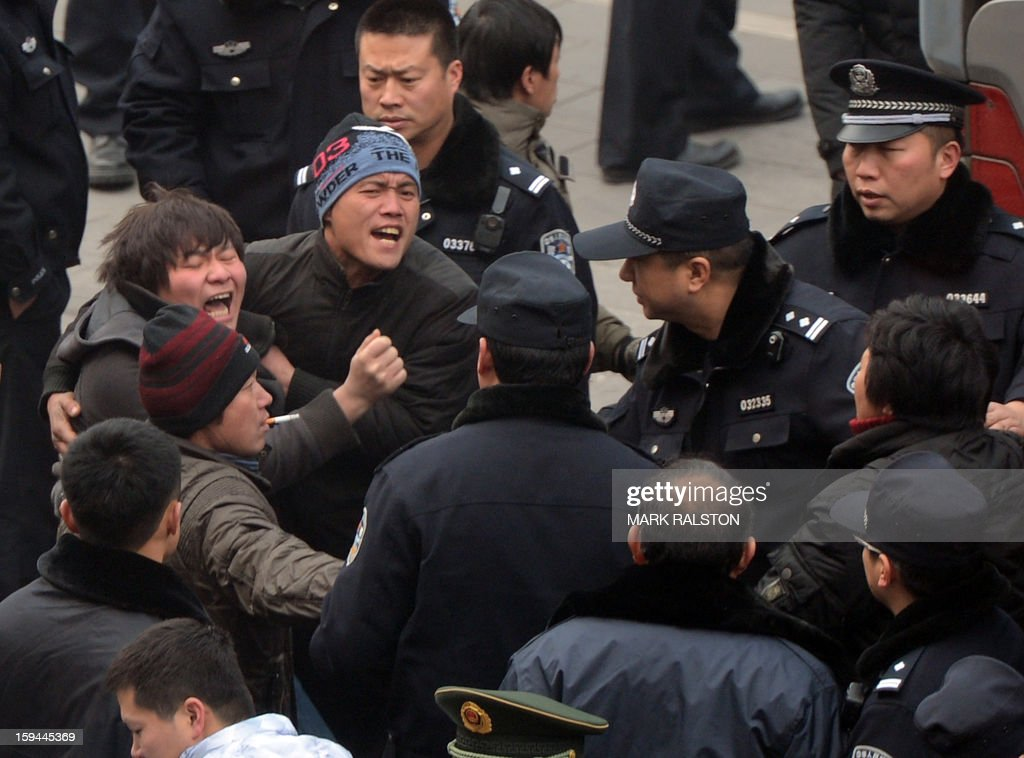 Chinese migrant workers confront police after staging a sit-in at the residence of a construction firm boss when the group of up to 50 migrant workers stormed past security at the Qijiayuan Diplomatic Compound to protest against what they claim is an unpaid new year bonus in Beijing on January 14, 2013. Labour unrest and disputes are common before the Chinese New Year when migrant workers are paid for their full years work in a lump sum before heading home to their famillies in outer provinces of the country. AFP PHOTO/Mark RALSTON