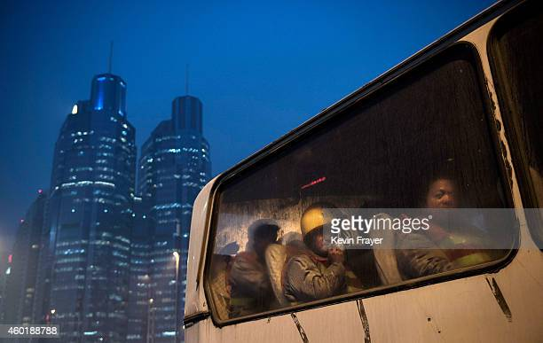 Chinese migrant workers wait in a bus as they leave after their shift at a construction site on December 9 2014 in Beijing China It is estimated that...