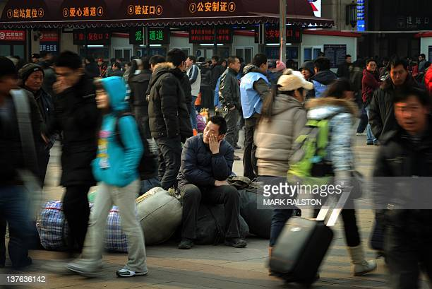 Chinese migrant workers wait to board their train home for the annual Chinese New Year holidays at the Beijing Train Station on January 15 2012 The...