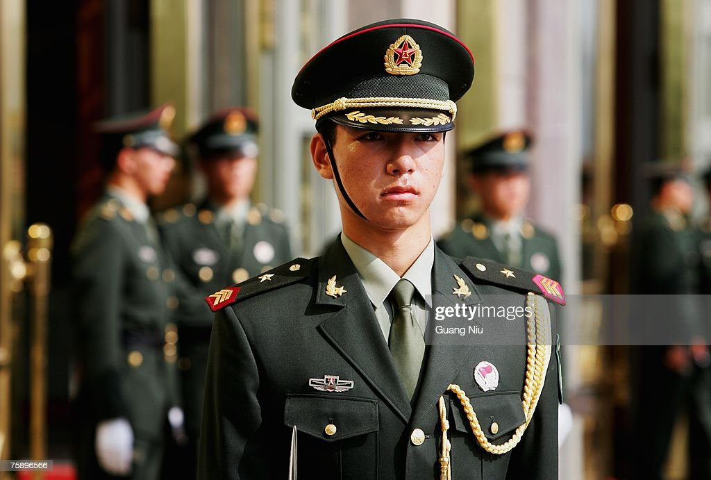 Chinese military officers with the new style military uniform guard an entrance of the Great Hall of the People where a meeting is held to mark the 80th anniversary of the founding of the People's Liberation Army (PLA) on August 1, 2007 in Beijing, China. The PLA, the world's largest standing army with 2.3 million members, celebrates its 80th anniversary on August 1.
